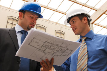 two architects reviewing blueprints